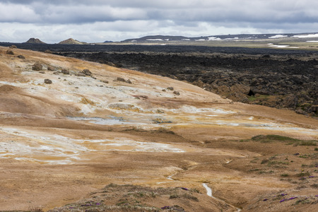 hot water geothermal: Geothermal landscape Krafla on Iceland with red dirt, steam and a hot water stream down a hill.