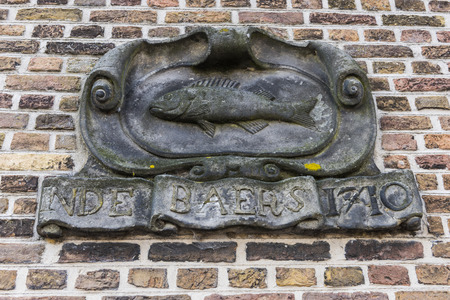 dordrecht: Statue in a wall of an old house with inscription: Inde Baers in the city of Dordrecht, The Netherlands.
