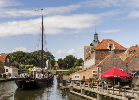 Enkhuizen, The Netherlands - August 9, 2016: Ship in the harbor of Enkhuizen with old houses, drommedaris and terrace with people.