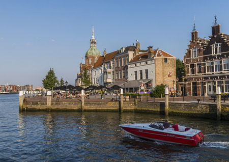dordrecht: Dordrecht, The Netherlands - September 13, 2016: Terrace in Dordrecht with Groothoofdspoort and motor boat on the water of the Merwede in Zuid-Holland, The Netherlands. Editorial