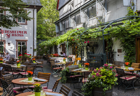 Rudesheim, Germany - August 20,2016: Terrace with wooden chairs and tables of Rudesheimer Schloss in Rudesheim near the Rhine.