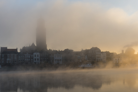 morning blue hour: Deventer at the IJssel in the morning during sunrise with the Great Church or Lebuinuskerk and fog  in the province Overijssel, The Netherlands. Editorial