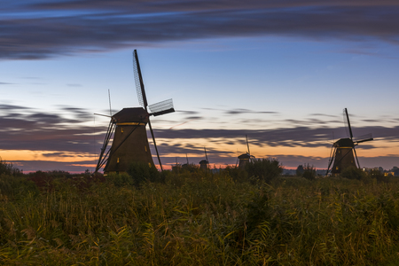 Sunrise at Kinderdijk   with orange blue sky and several wind mills in the Netherlands.
