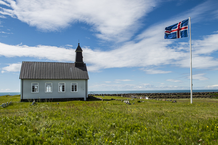 Strandkirkja on Iceland with Icelandic flag, green meadow and ocean. Stock Photo