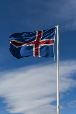 Flag of Iceland waving in de wind with blue sky.