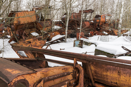 Rusty metal threshers in Chernobyl in the Exclusion zone in the Ukraine in wintertime. Stock Photo