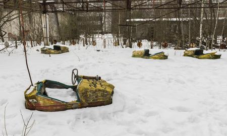 Chernobyl, Oekraïne - 19 februari 2017: Gele botsauto's in de sneeuw in Tsjernobyl in de radio-actieve dood zone in Ukrain.