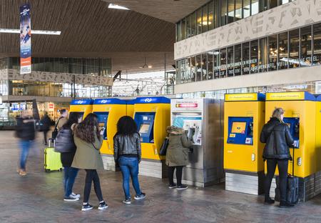 Rotterdam, Nederland - 10 maart, 2017: Reizigers die hun kaartjes krijgen bij de kaartjesautomaat in het station van Rotterdam in Nederland.