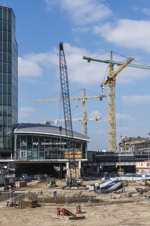 buildingsite: Utrecht, The Netherlands - March 23, 2017: Building site near central station of Utrecht with cranes, offices and workers, The Netherlands.