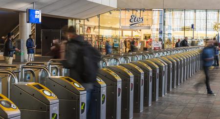 Rotterdam, Nederland - 10 maart, 2017: Reizigers bij de poorten voor OV Chip-kaartjes in het station van Rotterdam in Netheralnds. Redactioneel