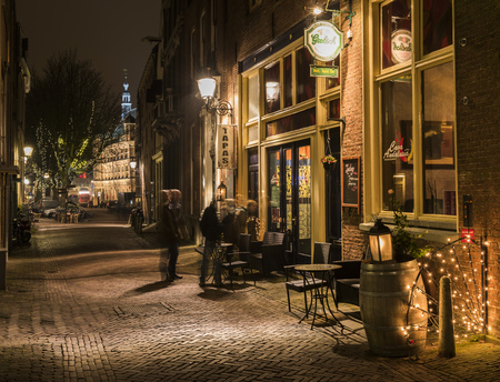 Deventer, The Netherlands - December 17, 2016: People at Tapas restaurant in the Polstraat (street) in Deventer during Christmas time in the evening with christmas lights, lanterns and a illuminated tower.