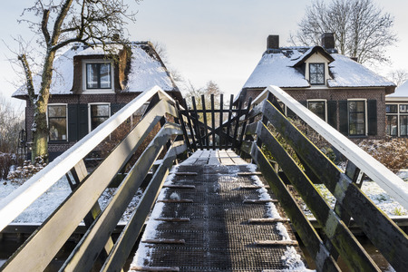 Giethoorn, The Netherlands - January 18, 2016: Winterlandscape with, canal, farmhouses and bridge in the typical dutch village of Giethoorn in the province of Overijssel in the Netherlands.
