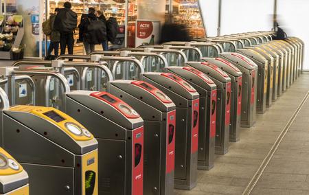 cs: Arnhem, The Netherlands - December 23, 2016: OV -chip gates for NS and Arriva at railway station Arnhem with shops.