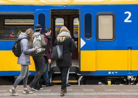 Rotterdam, Nederland - 10 maart 2017: Reizigers op het platform in de buurt van de deur van een trein in het treinstation Rotterdam in Nederland.