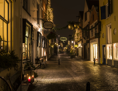 Deventer, The Netherlands - December 17, 2016: Walstraat (street) in Deventer during Christmas time in the evening with christmas lights and  lanterns during Dickens Festival. Editorial