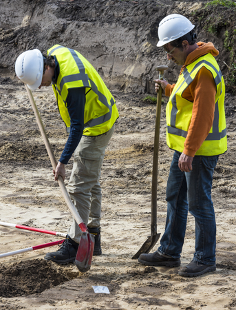 Driebergen, The Netherlands - March 22, 2017: Archeology excavation site with two man digging in the ground in Driebergen, The Netherlands.