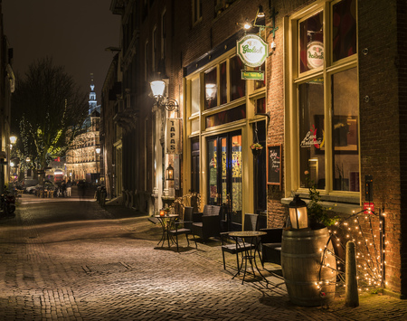 Deventer, The Netherlands - December 17, 2016: Tapas restaurant in the Polstraat (street) in Deventer during Christmas time in the evening with christmas lights, lanterns and a illuminated tower. Editorial