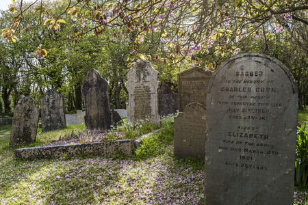 Gwithian, Engeland - 25 april 2017: Kerkhof in Gwithian met oude grafstenen, kruisen en bomen, Cornwall, Engeland.