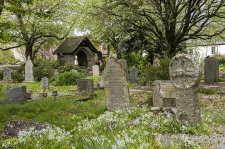 Gwithian, Engeland - 25 april 2017: Kerkhof in Gwithian met oude grafstenen, Keltisch kruis en bomen, Cornwall, Engeland.