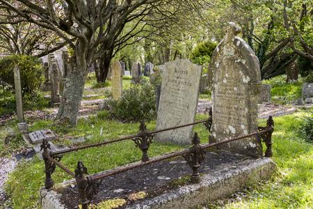 Gwithian, Engeland - 25 april 2017: Kerkhof in Gwithian met oude grafstenen, bluebells en bomen, Cornwall, Engeland.