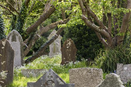 Gwithian, Engeland - 25 april 2017: Kerkhof in Gwithian met oude grafstenen en bomen, Cornwall, Engeland.