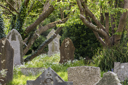 Gwithian, England - April 25, 2017: Graveyard in Gwithian with old gravestones and trees, Cornwall, Engeland.