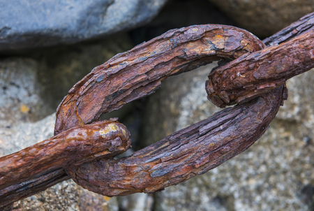Link of a rusty and strong chain on rocks.
