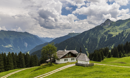Old wooden cabin and chapel in Matschwitz with in the background the mountains of Montafon on a summers day, Austria