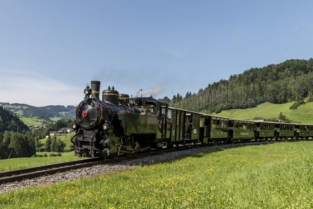 Bersbuch, Austria - July 22, 2017: Steam locomotive of the Bregenzerwaldbahn, 'Waelderbaenle', in the mountains of the Bregenzerwald, driving trough the alpine meadows, Austria.