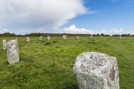 Merry Maidens stone circle on a grass field with great clouds in Cornwall, England.