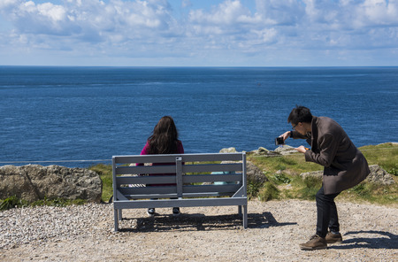 Lands End, England - April 27, 2017: Tourists sitting on bench at Lastfirst house at Lands End in summer taking pictures with phone. Editorial