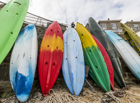 mousehole: Mousehole, England - April 28, 2017: Harbor of Mousehole with kayaks against a great stone wall of the quay, Cornwall.