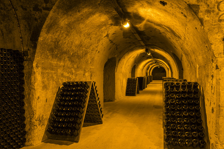 Reims, France - June 12, 2017: the caves of Champagne House taittinger with old bottles Champagne in pupitres, France. Editorial