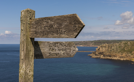 Lands End, England - April 27, 2017: Sign of coast path and public footpath in Cornwall with ocean and blue sky. Editorial