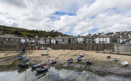 mousehole: Mousehole, England - April 28, 2017: Panorama of Mousehole with the harbor, houses and the tide, Cornwall.