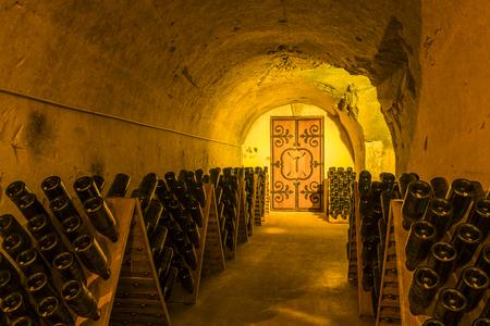 Reims, Frankrijk - 12 juni 2017: de grotten van Champagne House Taittinger met oude flessen Champagne in pupitres en deur van het oude klooster, Frankrijk.