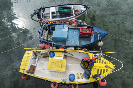 mousehole: Mousehole, England - April 28, 2017: Three fishing boats with nets, boxes, and ropes, Cornwall.