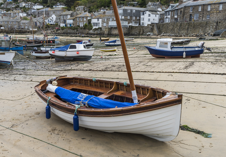 mousehole: Mousehole, England - April 28, 2017: Harbor of Mousehole with fishing boats, sail boat, houses and low tide, Cornwall. Editorial