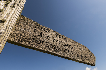sennen: Lands End, England - April 27, 2017: Sign of coast path and public footpath in Cornwall with ocean and blue sky. Editorial