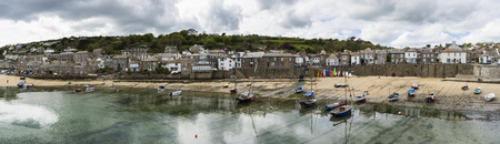 mousehole: Mousehole, England - April 28, 2017: Panorama of Mousehole with the harbour, houses and the tide, Cornwall