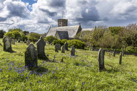 Pendeen, England - April 26, 2017: Church and cemetery with gravestones in Pendeen with dark clouds and sunlight, Cornwall, England.
