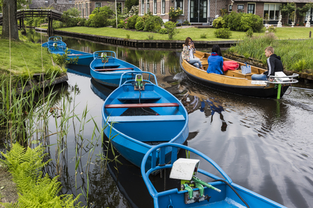 Giethoorn, The Netherlands - May 19., 2016:  Blue Punter Boats in the small, picturesque town of Giethoorn and Chinese tourists in electric boat, Overijssel, Netherlands.