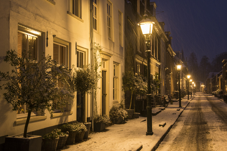 Wijk bij Duurstede, Netherlands - December 11, 2017: Volderstraat street in december during Xmas and winter blizzard with houses, lanterns and snow. Stockfoto - 93669338