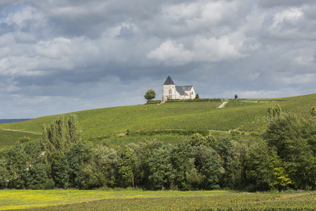 Church of Chavot-Courcourt with the sun on the church, dark rain clouds in the sky and the champagne vineyards in front, France. Banco de Imagens