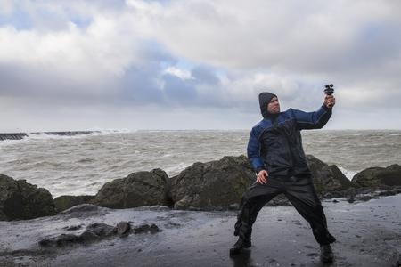IJmuiden, Holanda - 18 de enero de 2018: Hombre en tormenta con medidor de viento en el Mar del Norte en el Zuidpier en IJmuiden en Noord-Holland. Editorial