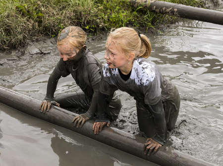 Biddinghuizen, The Netherlands - June 23, 2018: Children, girls, during a mudrun (mudraise) in the mud and in the water climbing a tree trunk. Editöryel