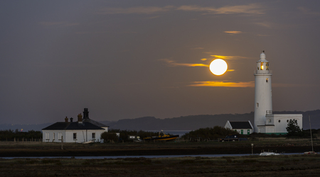 Hurst Point Lighthouse with some white houses and full moon rising early in the night near Keyhaven and  the beach. 스톡 콘텐츠