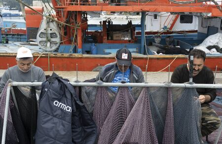 Sinop, Tukey - May 3, 2019: Three fishermen are working on and repairing  fishing nets in the harbor of Sinop with orange fishing boat in the background.