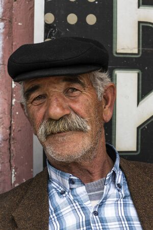Susuz, Turkey - May 9, 2019: Turkish man with hat, moustache and beard in a turkish cafe. Redactioneel