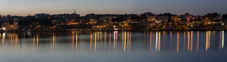 Gerze, Turkey - May 4, 2019: Panorama of the city og Gerze with harbor and Black Sea during dusk and night with many lights and reflections in the water.